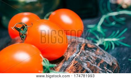 Red fresh cherry tomatoes and rosemary twigs on wood cutting board and on black table. Close-up