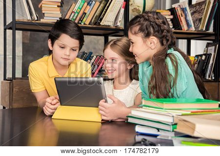 Three smiling schoolchildren using digital tablet in library