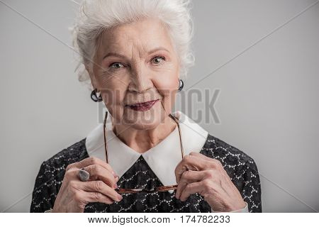 I remember days. Portrait of happy elderly woman holding her glasses in hands and posing while standing. isolated on background
