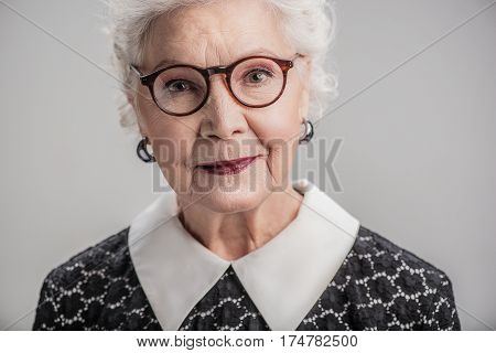 Count your age by memories not years. Portrait of friendly elderly female wearing glasses with smile isolated on gray background
