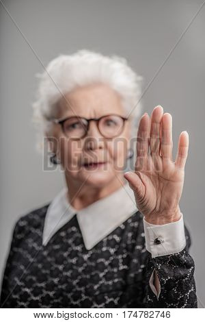 Stop it. Portrait of Confident middle aged woman showing her palm isolated on gray background. Focus on her hand