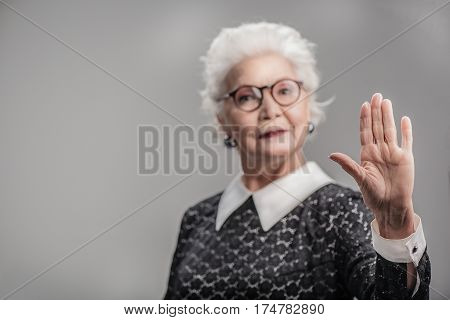 Be yourself. Portrait of senior lady gesturing stop with palm of her hand against gray background. Focus on her hand