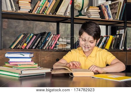 Smiling schoolboy sitting at table and reading book in library