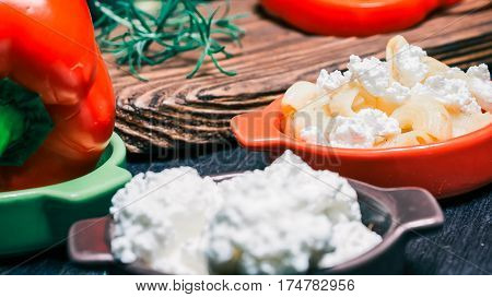 Pasta elbows, white cheese and red pepper on dark wood cutting board and on black table. Close-up