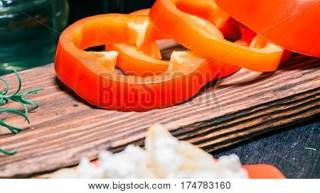 Sliced red paprika, thyme and rosemary on wood cutting board and on black table. Close-up