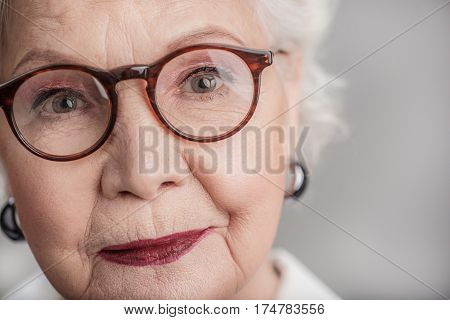 I miss old time. Close up portrait of senior woman smiling and looking at camera through glasses. Isolated on gray background