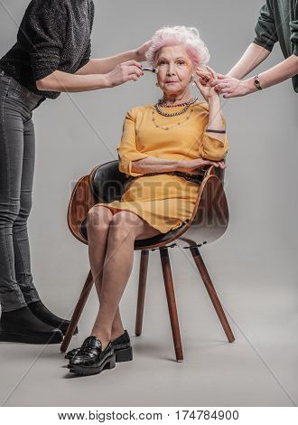 She always dresses fashionably. Makeup artist and stylist working in tandem with attractive elderly woman. isolated on gray background