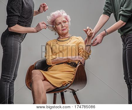 Young at heart. Stylist and makeup artist preparing attractive grey haired senior woman for photo shoot. isolated on gray background
