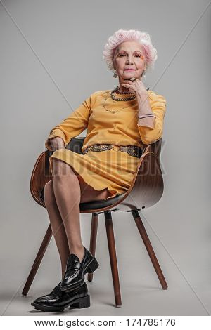 Facing old age with optimism. Portrait of Elderly stylish lady beauty touching her face, isolated on gray background, while sitting on chair