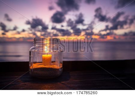 Candle lamp on wooden table with sea and sunset background romantic dinner in the restaurant. Indonesia Bali