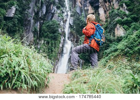 Tourist man with backback rest near the waterfall in rainy forest