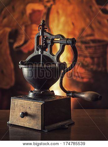Huge old coffee grinder on wooden table. Vintage toned.