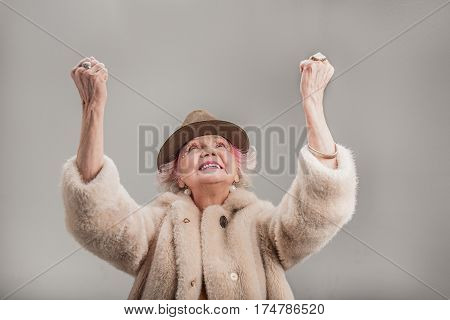 Happy winner. Smiling elderly woman wearing fur coat and keeping arms raised while standing. isolated on gray background