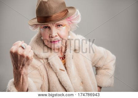 I am very furious. Portrait of angry old woman in fur coat and hat shaking her fist while standing. isolated on gray background