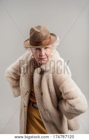 Forget your age. Portrait of Elegant senior woman in hat and fur coat posing. isolated on gray background