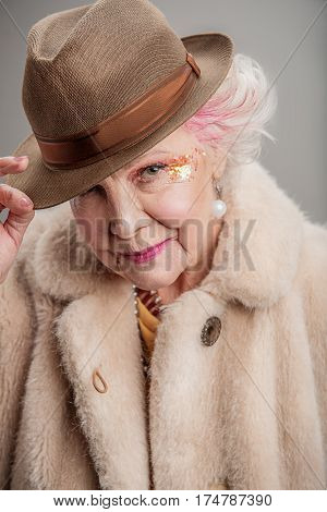 What is up man. Portrait of confident beautiful senior stylish lady wearing fur coat and brown hat while standing. isolated on gray background