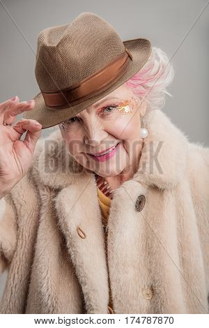 Happiest years of my life. Portrait of Happy pleasant senior lady posing in fur coat with bright makeup and smiling. isolated on gray background