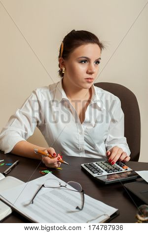 Young woman bookkeeper considers on calculator