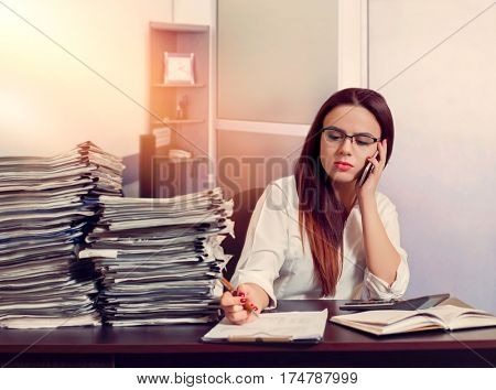 Woman bookkeeper using mobile phone at workplace