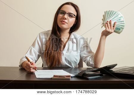 Female bookkeeper holding dollars fan in her hand