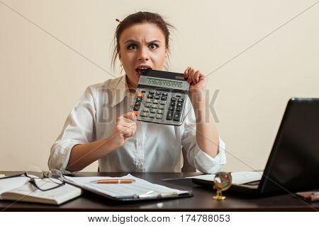 Afraid female bookkeper gnaws calculator