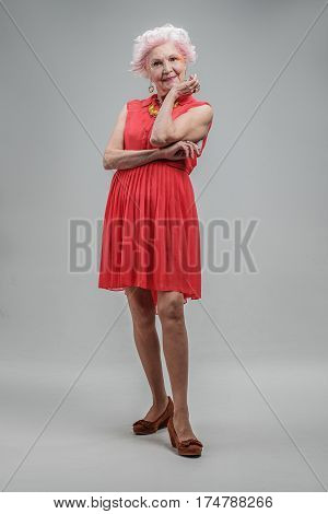 Lost in thoughts of yesterday. Smiling elderly stylish lady wearing red dress and holding hand on her chin. isolated on gray background