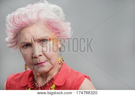 Thinking about important things. Portrait of Senior modern woman with bright makeup feeling upset and looking at camera. isolated on gray background