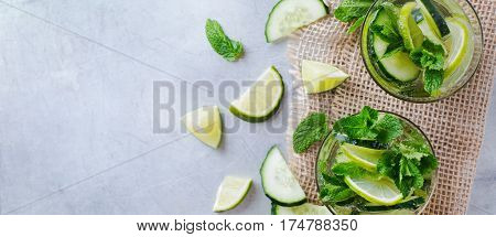 Healthcare, fitness, healthy nutrition concept. Fresh cool cucumber lime mint infused water, cocktail, detox drink, lemonade for spring summer days. Top view overhead flat lay, copy space background