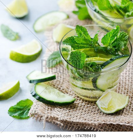 Healthcare, fitness, healthy nutrition concept. Fresh cool cucumber lime mint infused water, cocktail, detox drink, lemonade for spring summer days