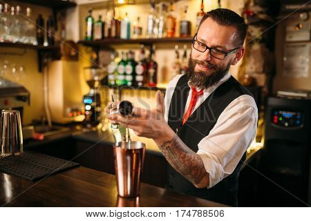 Bartender pouring alcohol beverage in metal glass