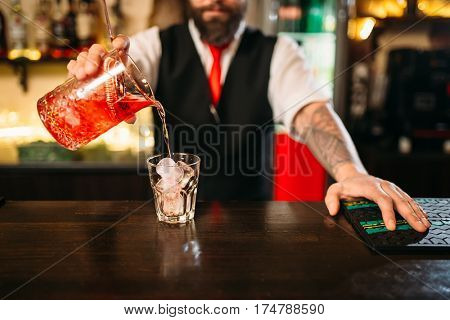 Barman pouring alcoholic drink in glass