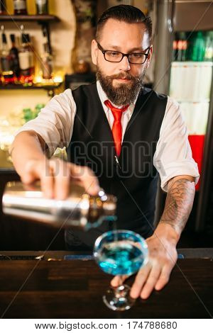 Barman with shaker making alcohol cocktail