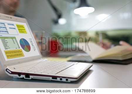 Business Meeting at grey Office Table with white portable Computer and professional Chart on Screen Papers Notepad Mugs on blurred Background