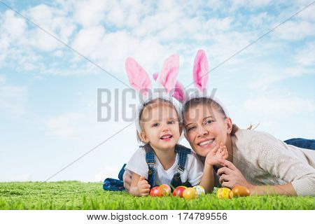 Easter bunny. Little girl with mother dressed as the Easter bunny lying on the grass with painted easter eggs.