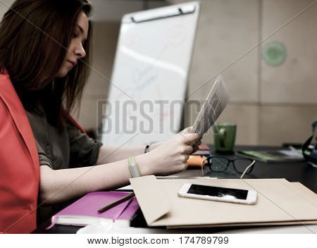 Young female Lawyer reading printed Document Business Items and Stationery dropped around Envelope Telephone Glasses Notepad Mug and Flip Chart on Background