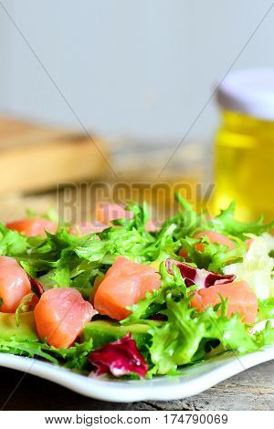 Fresh salad mix with smoked salmon and avocado and dressing with olive oil and lemon juice. Healthy and quick salad on a plate. Vertical photo. Closeup