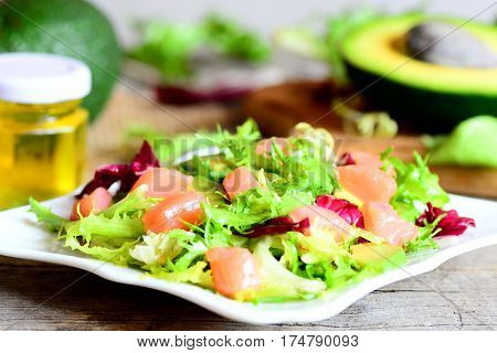 Mixed green salad with smoked salmon and avocado and dressing with olive oil and lemon juice. Vegetarian and quick salad on a plate. Vintage style. Closeup