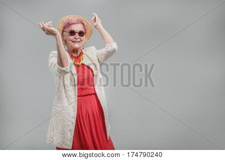 Life is good. Portrait of Senior modern woman expressing positive emotions while dancing and smiling. isolated on gray background