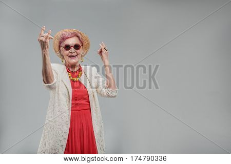 My lifetime full of happiness. Smiling fashionable old female wearing sunglasses and having fun while dancing with hands up. isolated on gray background. Copy space