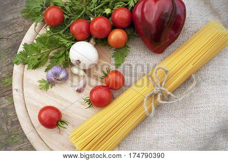 Pasta spaghetti and fresh vegetables. Tomato, garlic, onion, paprika.