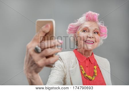 I like posing. Portrait of Happy elderly female with fashionable hairstyle doing selfie with her smart phone while smiling. isolated on gray background