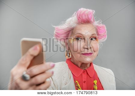 Be in trend. Portrait of Beautiful elderly woman with bright makeup posing while making selfie and standing. isolated on gray background