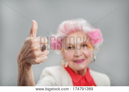 Everything is fine. Smiling stylish elderly female giving thumb up while looking at camera against gray background. Focused on hand
