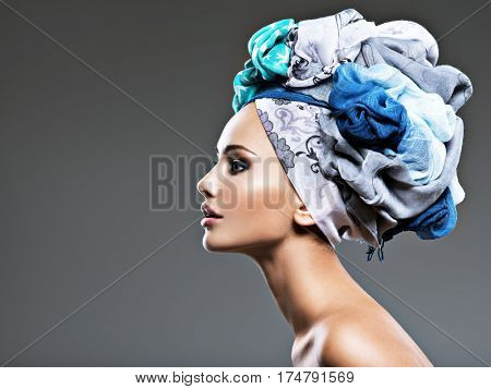 Profile portrait of beautiful  girl  in turban. Creative portrait of fashion woman. Young model posing at studio