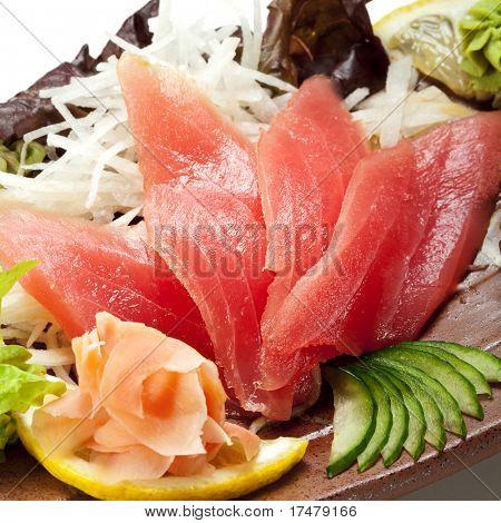 Tuna Sashimi - Maguro (fresh raw tuna) on Daikon (White Radish). Garnished with Ginger, Wasabi, Seaweed, Cucumber, Salad Leaf and Lemon
