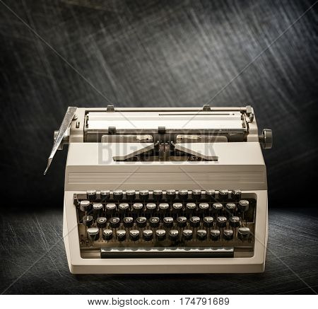 Typewriter with latin alphabet on steel scratchy background