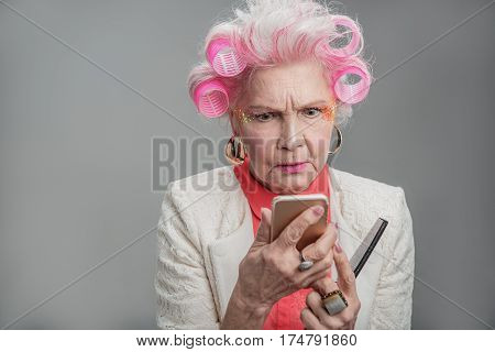 Thinking of perfect reply. Portrait of Senior woman in curlers and bright makeup using smartphone while looking confused. isolated on gray background