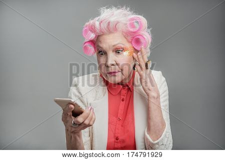 I am very surprised. Shocked elderly female holding hand on chin while looking at smartphone and standing isolated on gray background