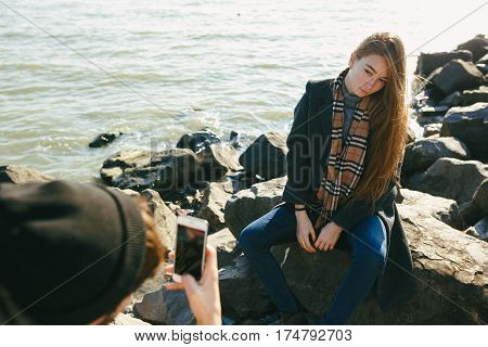 Beautiful And Stylish Couple Are Photographed On A Rocky Beach. Couple Dressed In Jackets, Hats And