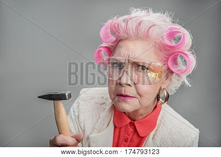 Whom are you calling old. Portrait of Stylish elderly woman in curlers holding hammer while posing at camera. isolated background